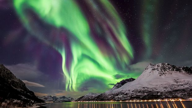 <p>Aurora Boreal sobre um fiorde, na Noruega. As cores são produzidas a diferentes altitudes por diversos gases atmosféricos, sendo o azul emitido pelo nitrogênio e verde pelo oxigênio. Vermelho pode ser produzido por ambos, enquanto roxo, rosa e amarelo ocorrem quando há mistura de cores</p>