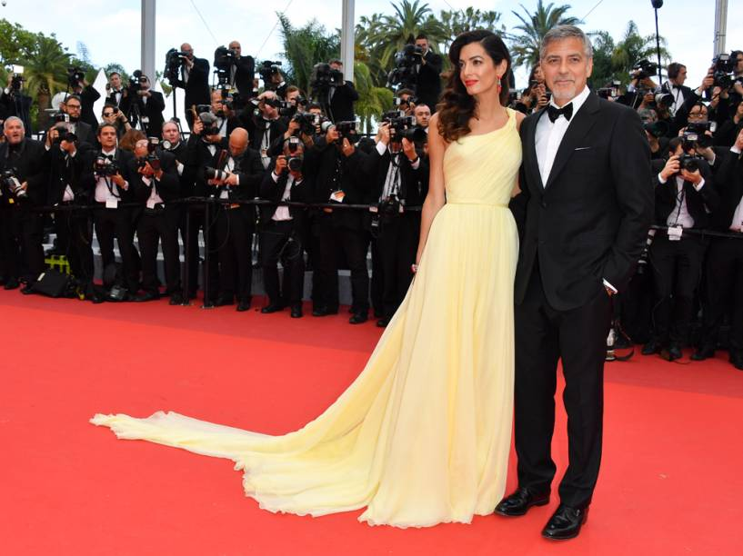 Amal Clooney, sempre elegantérrima, vestiu um Versace amarelo de um ombro só e caimento solto para acompanhar o marido, George Clooney, na première de Jogo do Dinheiro