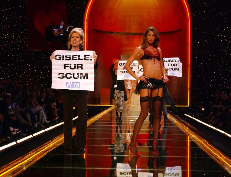 """Em 2002, ativistas do grupo PETA invadiram a passarela de um desfile em Nova York para protestar contra campanha em que a modelo usava peles de animais. Os cartazes traziam a escrita """"Gisele: fur scum"""", em português algo como """"Gisele: escória coberta de pele"""""""