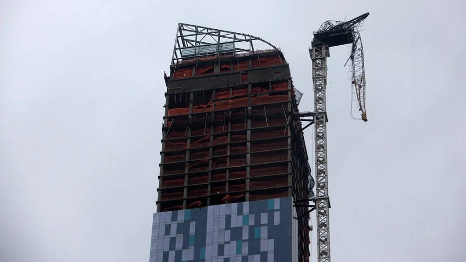 Um guindaste fica pendurado ao lado de um prédio em construção em Nova York
