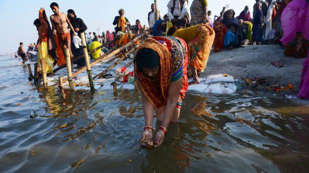 Indiana faz uma oferenda no Sangam, local de confluência dos rios sagrados Ganges, Yamuna e Saraswatu, durante o Mauni Amavasya, dia considerado mais auspicioso da celebração do Kumbh Mela, em Allahabad, na Índia