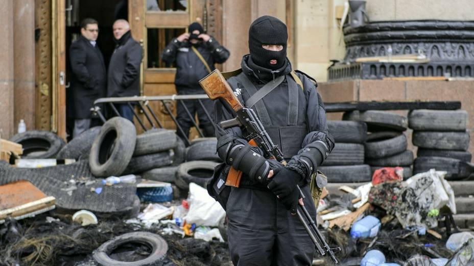 Homem armado representando as forças especiais da Ucrânia monta guarda em frente a um prédio público ocupado anteriormente por manifestantes pró-Rússia
