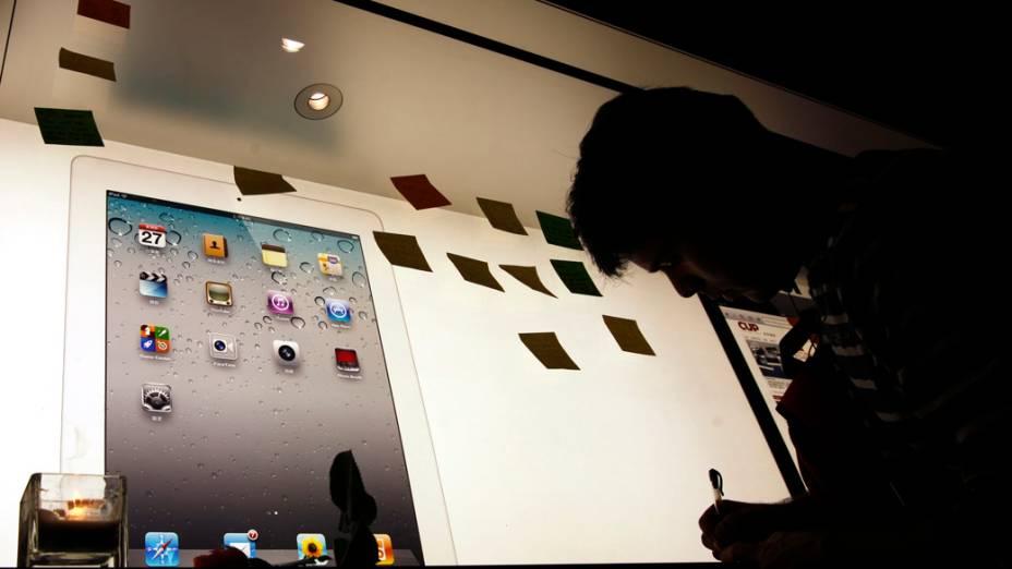 Homem escreve uma nota em homenagem a Steve Jobs em uma loja da Apple em Hong Kong, China
