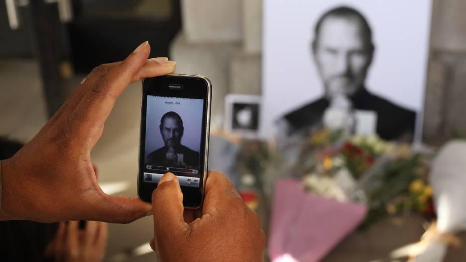 Homem fotografa tributo a Steve Jobs com um iPhone em frente a uma loja da Apple em Londres