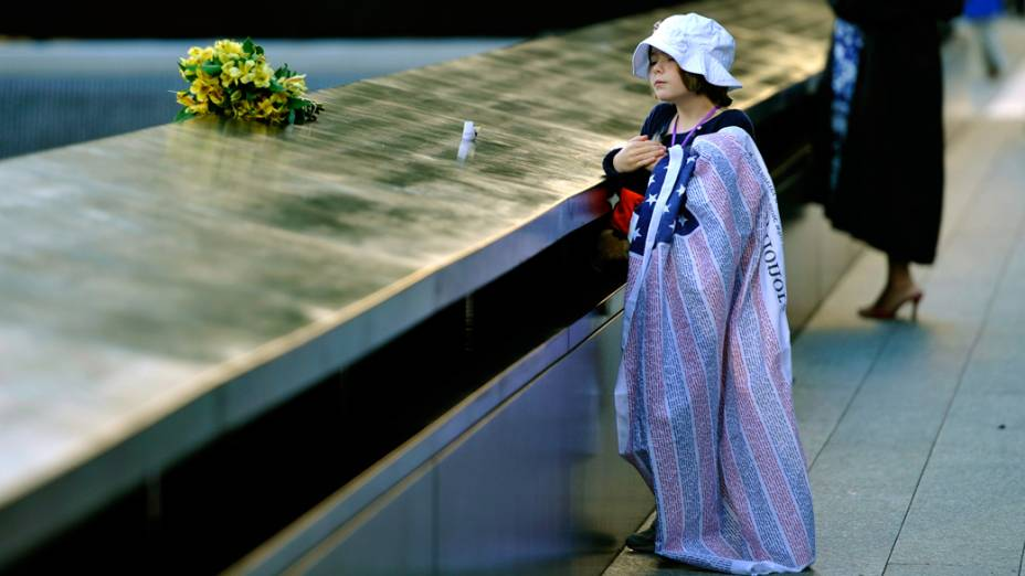 Ava Kathleen Schmoelzer, 7 anos coloca flores no memorial dedicado aos mortos do ataque ao World Trade Center