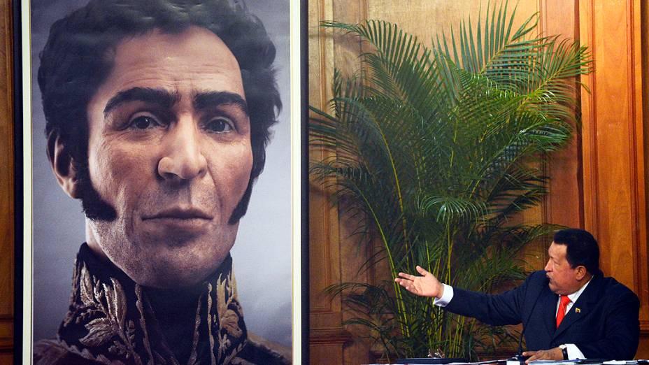 Chávez ao lado de imagem do rosto do herói da independência venezuelana, Simon Bolívar. A imagem é uma reconstrução digital a partir do crânio e do material genético do corpo de Bolívar