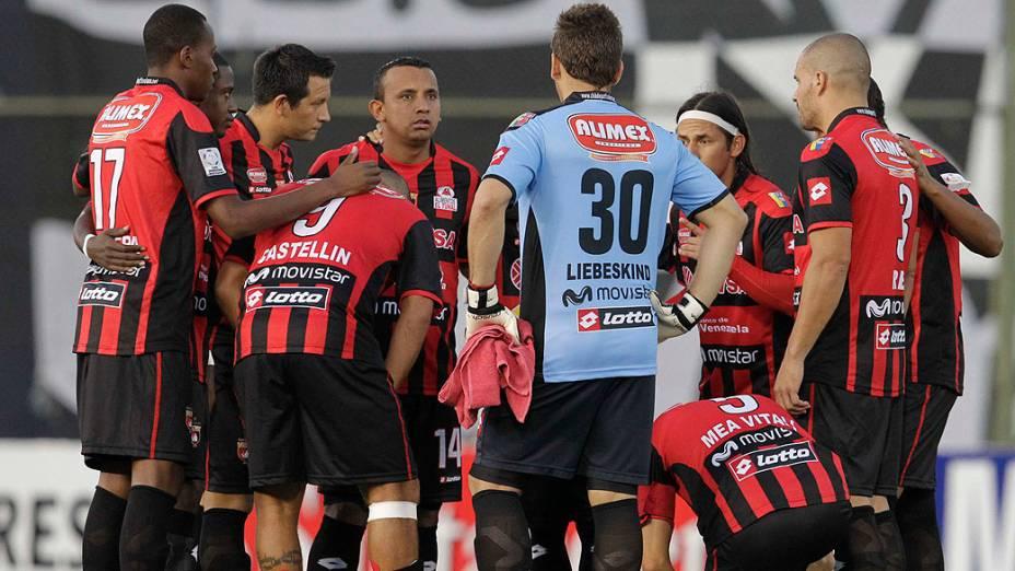 Jogadores venezuelanos do Deportivo Lara lamentam ao saber da morte de Hugo Chávez, recebida antes da partida contra o time paraguaio Olímpia pela Libertadores da América, em Assunção