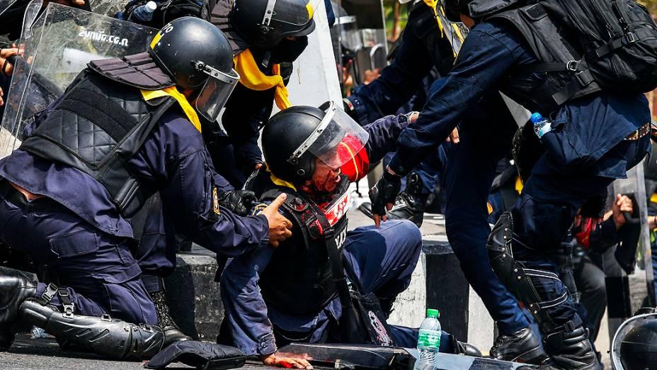 Policiais tailandeses socorrem colega durante confronto com manifestantes em Bangcoc, nesta terça-feira (18)