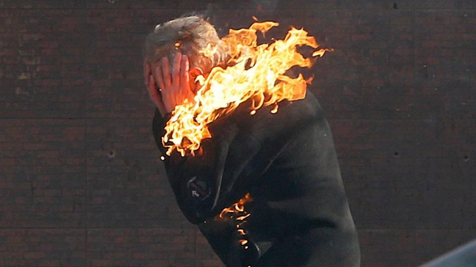 Um manifestante corre em chamas durante confronto com a polícia em Kiev, nesta terça-feira (18)