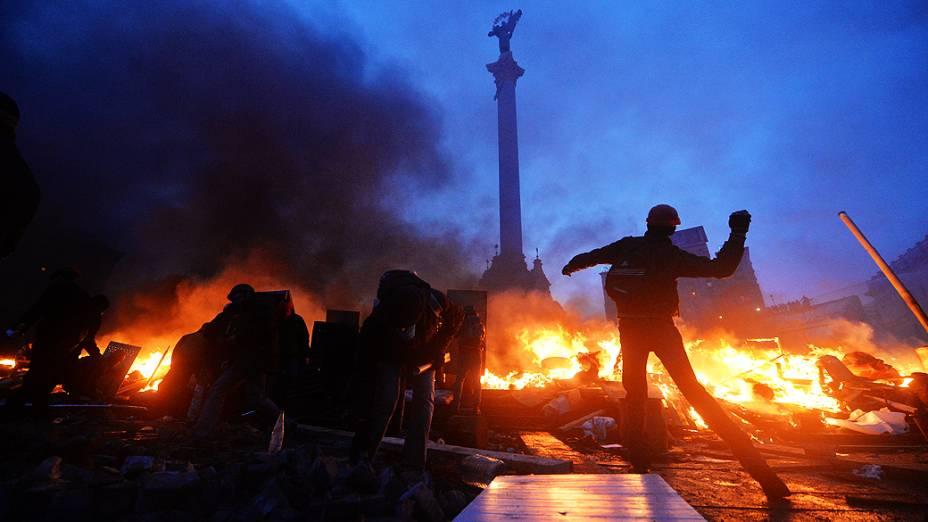 Homem se prepara para atirar uma bomba durante confronto com policiais no centro de Kiev, na Ucrânia, na manhã desta quarta-feira (19)