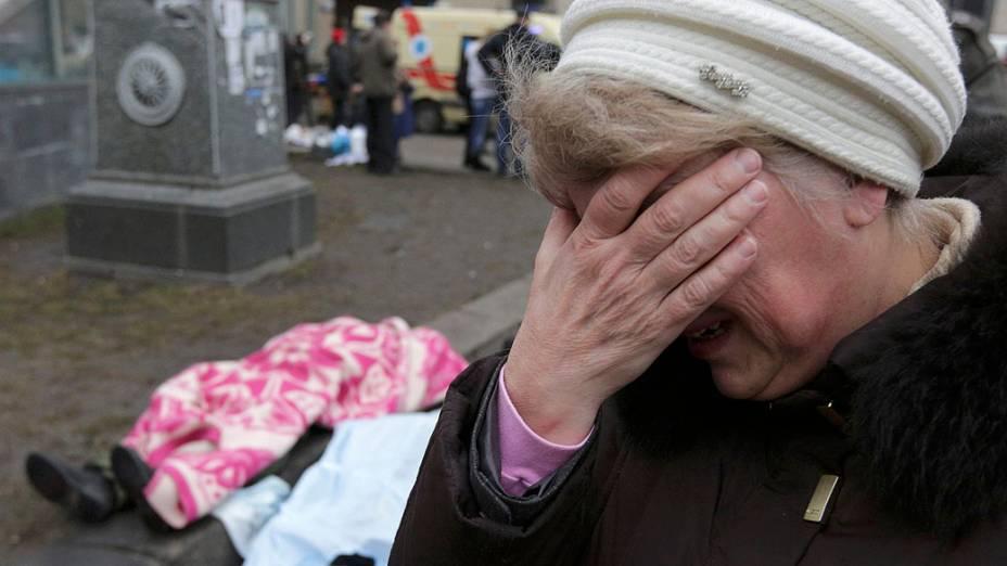 Mulher chora diante de dois corpos na na Praça da Independência, em Kiev