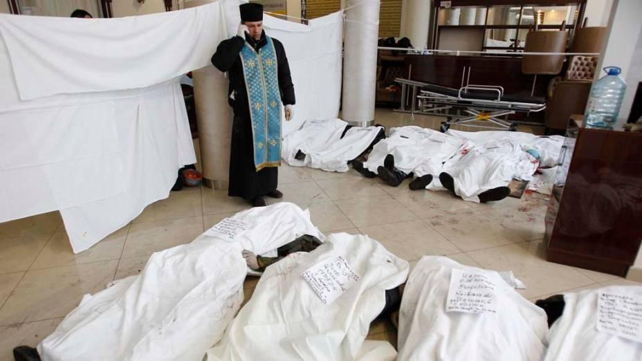 Em um hotel de Kiev, padre fala ao telefone perto de corpos de manifestantes mortos durante confrontos com a polícia
