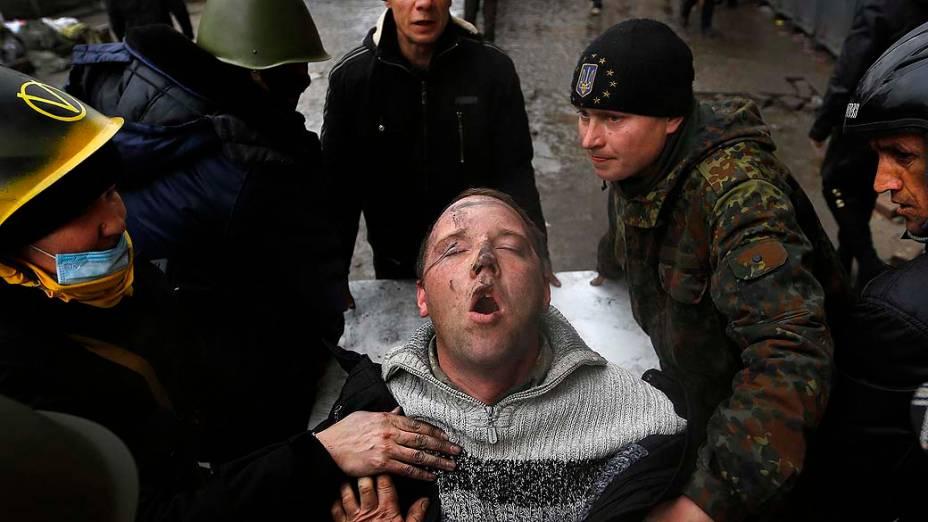 Homem ferido é socorrido em Kiev, na Ucrânia
