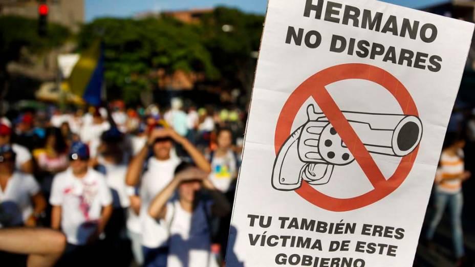"""Placa com a frase: """"Irmão, não atire. Você também é uma vítima deste governo"""" durante protestos em Caracas"""