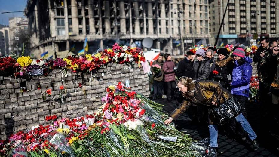 Mulher coloca flores diante de uma barricada na Praça da Independência em Kiev, nesta segunda-feira (24), homenageando os mortos nos confrontos que acabaram por derrubar o presidente ucraniano