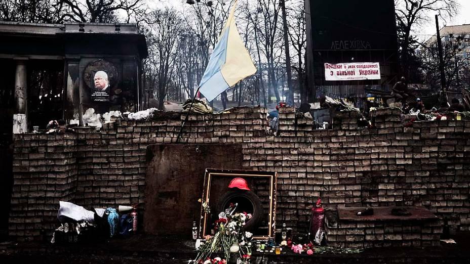 Ucranianos deixam flores em barricadas em memória dos mortos em confrontos na Praça da Independência, em Kiev, nesta terça-feira (25)