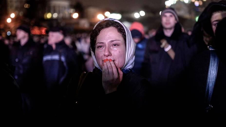 Mulher chora diante de uma barricada na Praça da Independência em Kiev, nesta terça-feira (25)