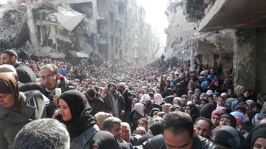 Em imagem divulgada nesta quarta-feira (26), multidão de moradores do bairro al-Yarmouk, transformado em campo de refugiados no sul de Damasco, aguarda a distribuição de alimentos pela agência UNRWA, da ONU