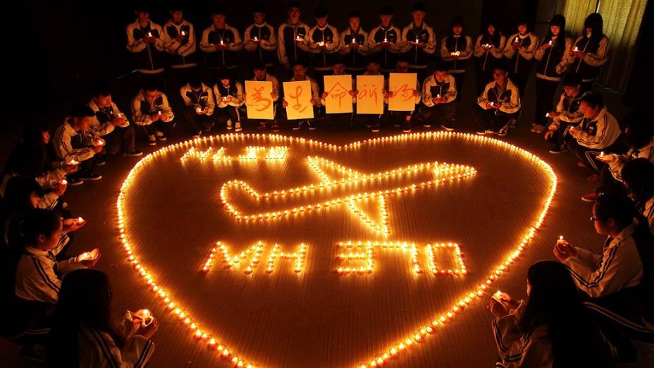 <p>Estudantes chineses acendem velas e rezam pelos passageiros do voo desaparecido da Malaysia Airlines</p>