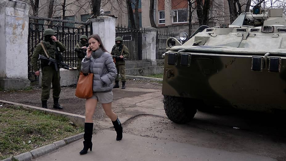 Mulher passa por soldados russos na sede da Marinha em Simferopol. O Tribunal Constitucional da Rússia decidiu por unanimidade que o presidente Vladimir Putin agiu legalmente ao incorporar a região da Crimeia à Rússia