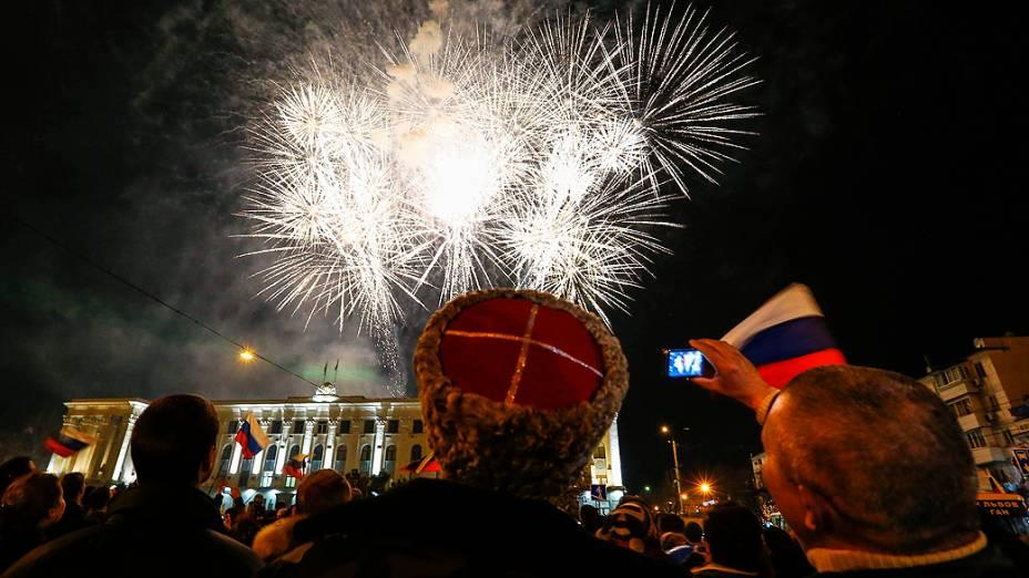 Fogos de artifício explodem sobre a praça central de Simferopol, na Crimeia, enquanto moradores celebram a primeira sexta-feira como parte da Rússia