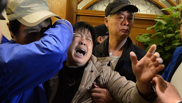 <p>Em Pequim, parentes dos passageiros do voo da Malaysia Airlines MH370 após ouvirem a notícia de que o avião caiu no Oceano Índico</p>