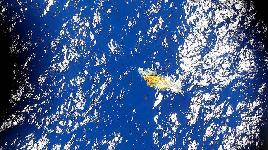 <p>Um pedaço de detrito flutua no local onde são realizadas as buscas ao voo desaparecido da Malásia Airlines, ao sul do Oceano Índico</p>