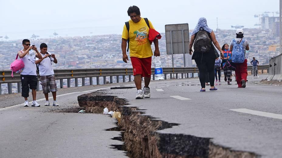 Pessoas caminham ao longo de uma estrada rachada após um novo terremoto em Iquique, norte do Chile