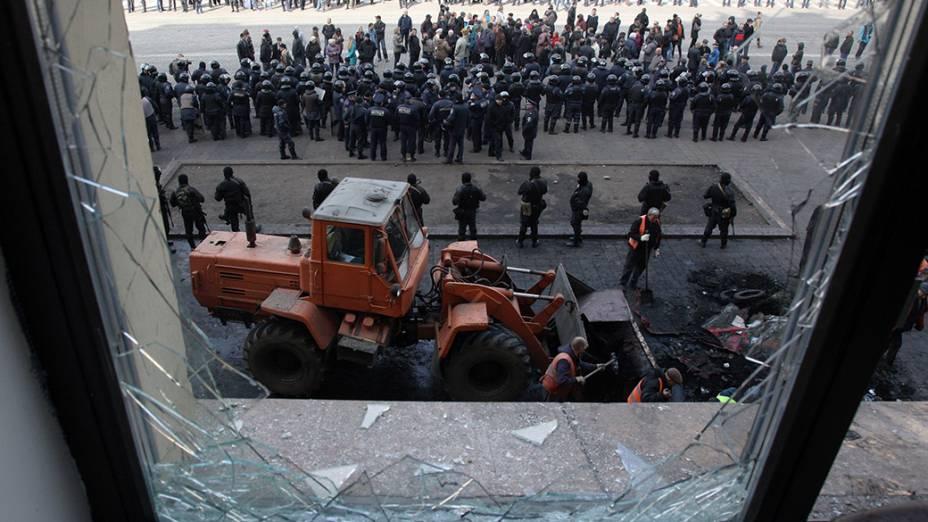 Trabalhadores limpam barricada construída por separatistas pró-Rússia em frente ao prédio administrativo de Carcóvia, na Ucrânia