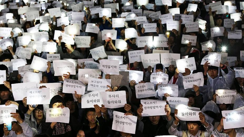 Estudantes Danwon High School seguram cartazes com mensagens para seus amigos que estão desaparecidos, após o desastre da balsa que naufragou com 475 passageiros em Jindo, na Coreia do Sul