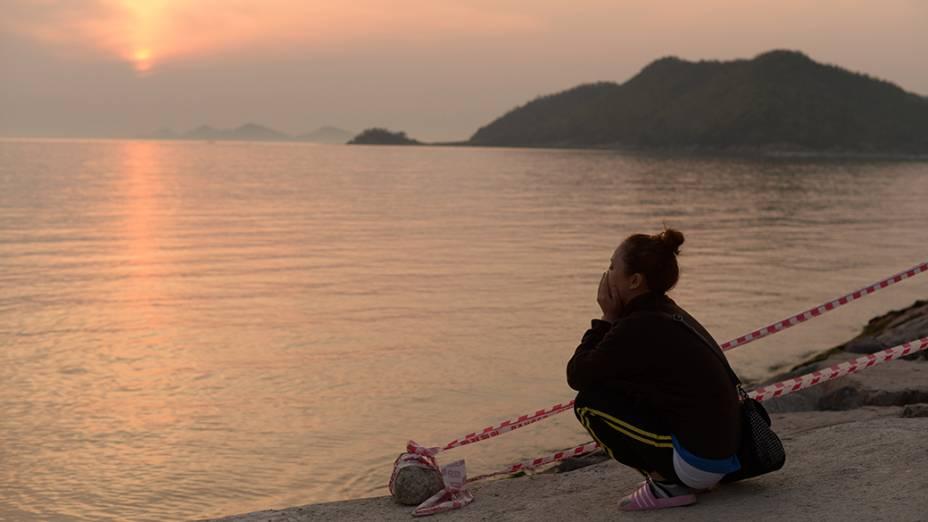 Um parente de uma vítima da balsa que naufragou na Coréia do Sul reza junto ao mar no porto de Jindo