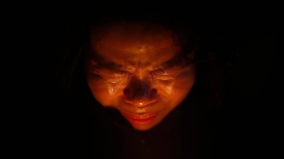 Mulher chora enquanto reza durante uma vigília à luz de velas em Ansan, para homenagear as vítimas da balsa de passageiros que naufragou na Coreia do Sul