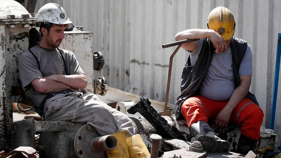 Mineiros descansam em frente à mina de carvão que na terça feira sofreu uma explosão, deixando mais de 280 mortos