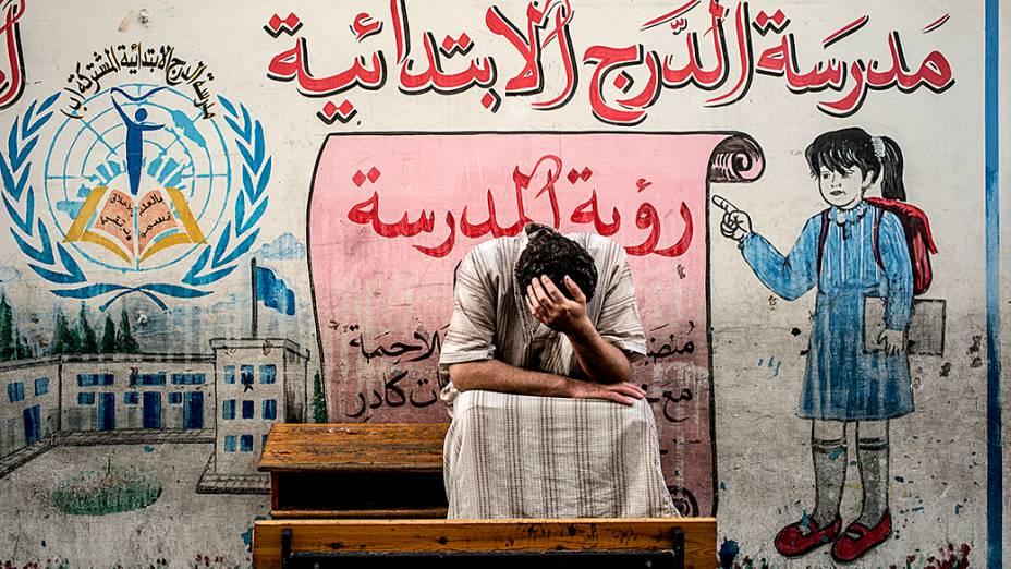 Palestino deslocado do bairro Shejaiya na Faixa de Gaza senta em um banco de uma escola administrada pela ONU, onde se juntou a outros que se refugiaram no local para fugir dos pesados combates em sua área