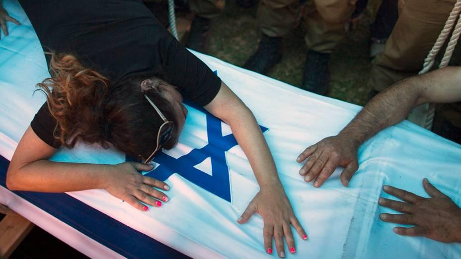 A mãe desoldado israelense chora sobre a bandeira nacional durantefuneral do filho, em Rishon Lezion, região próxima aTel Aviv. Israel abateu alvos em toda a Faixa de Gaza nestaterça-feira (22), contrariando pressões de diplomaciais internacionais para umcessar-fogo iumediato na região. Os conflitos já fizeram mais de 500 mortos entre pelestinos e israelenses