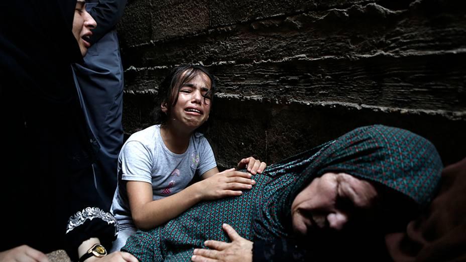 Parentes de um palestino de 60 anos morto após ataques do exército israelense, choram durante seu funeral na cidade de Gaza