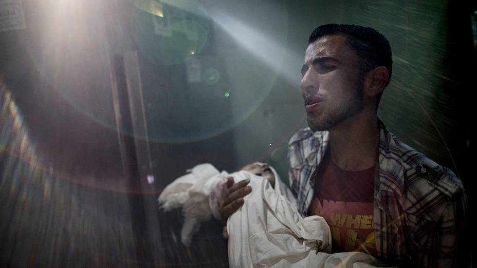 Pai segura o corpo do filho mortopor estilhaços de um tanque israelense, no hospital Kamal Adwan, ao norte da Faixa de Gaza, em 24/07/2014.O Secretário de Estado norte-americano, John Kerry, declarou que osesforços globais para acabar com 16 dias de conflito na região devem continuar