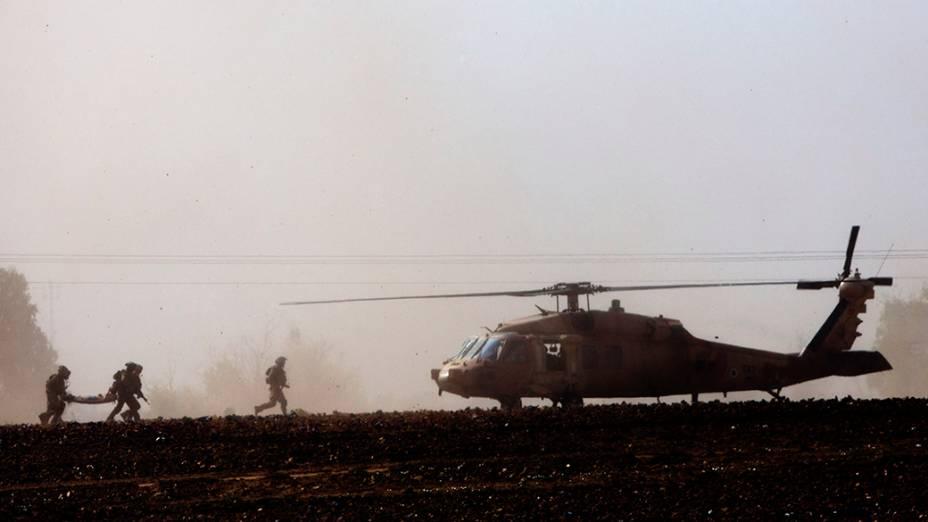 Israelenses carregam um soldado ferido para um helicóptero, perto da fronteira com a FaixaGaza,nesta quinta-feira (24). Os conflitos se intensificaram na região há três semanas, e o número de mortos já passa de 600