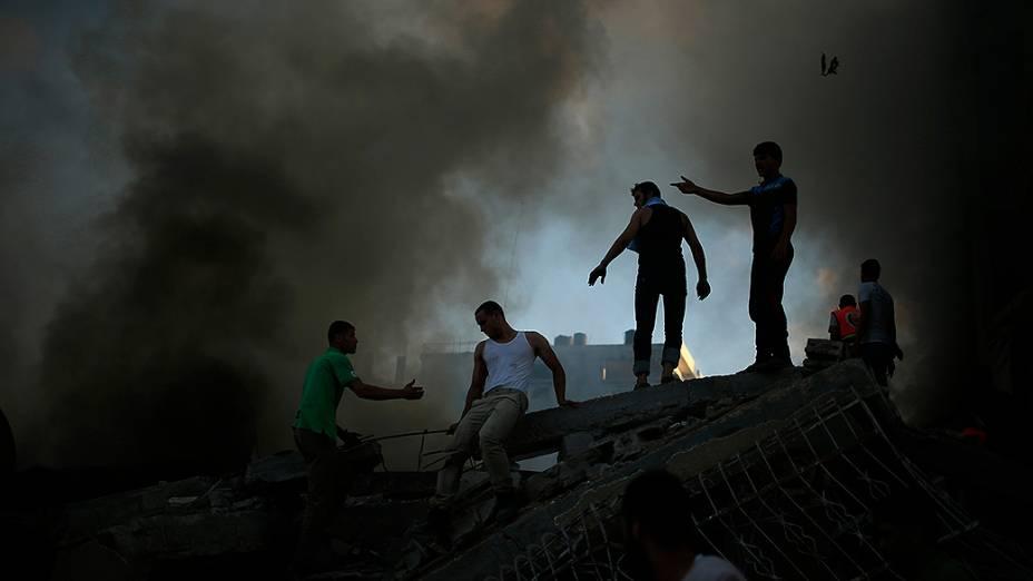 Palestinos tentam extinguir um incêndio após ataque aéreo israelense a um edifício na cidade de Gaza