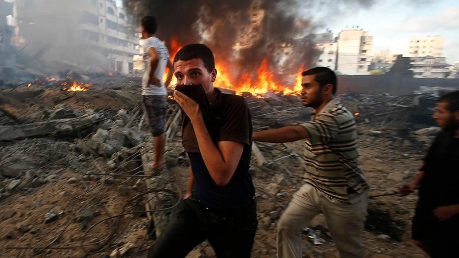 Palestinos passam por edifício incendiado após ataque aéreo israelense na cidade de Gaza
