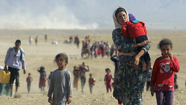 Iraquianos da minoria religiosa Yazidi fogem à pé em direção a Síria após ataques de militantes islâmicos que mataram pelo menos 500 pessoas que seguem a religião curda e católicos