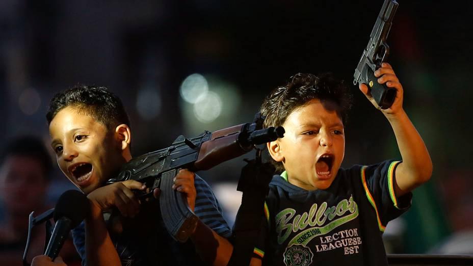 Crianças palestinas seguram armas em comemoração ao acordo de cessar-fogo sem tempo limitado fechado entre Hamas e Israel