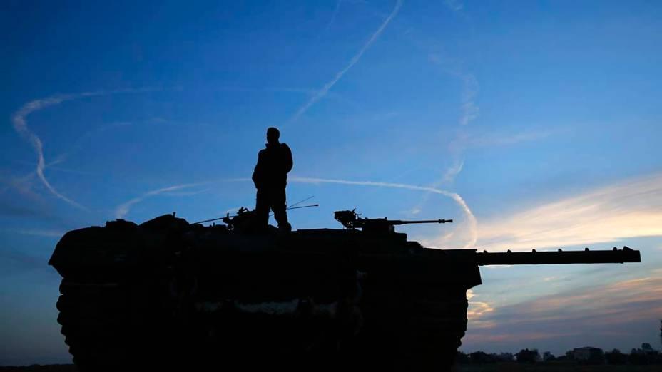 Soldado israelense observa fumaça deixa por caças da Força Aérea durante testes ao norte da faixa de Gaza