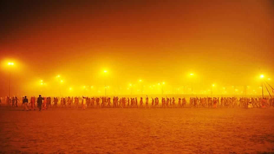 Peregrinos hindus fazem procissão em direção ao Sangham, confluência dos rios Ganges e Yamuna, para se banhar antes do nascer do sol durante o Kumbh Mela em Allahabad, Índia