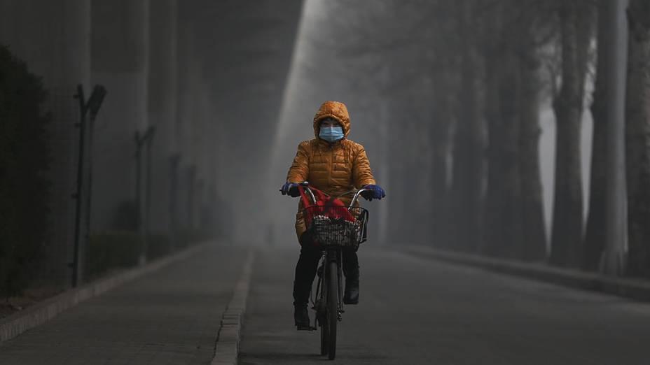 Mulher anda de bicicleta usando máscara durante forte poluição em Pequim, China