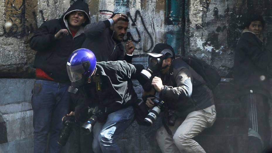Fotógrafos se protegem enquanto manifestantes atiram pedras em direção a polícia da Praça Tahrir, no Cairo