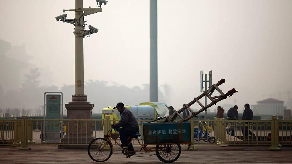 Trabalhador anda num triciclo, na província chinesa de Henan, em dia de forte neblina, agravada pela poluição do país