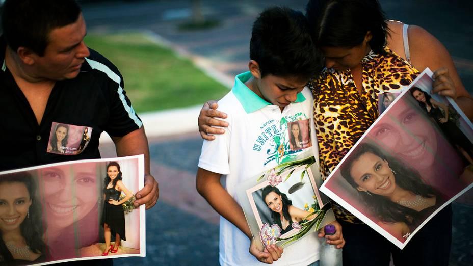 Com um cartaz mostrando foto de vítima do incêndio, menino chora com seus pais em Santa Maria (RS)