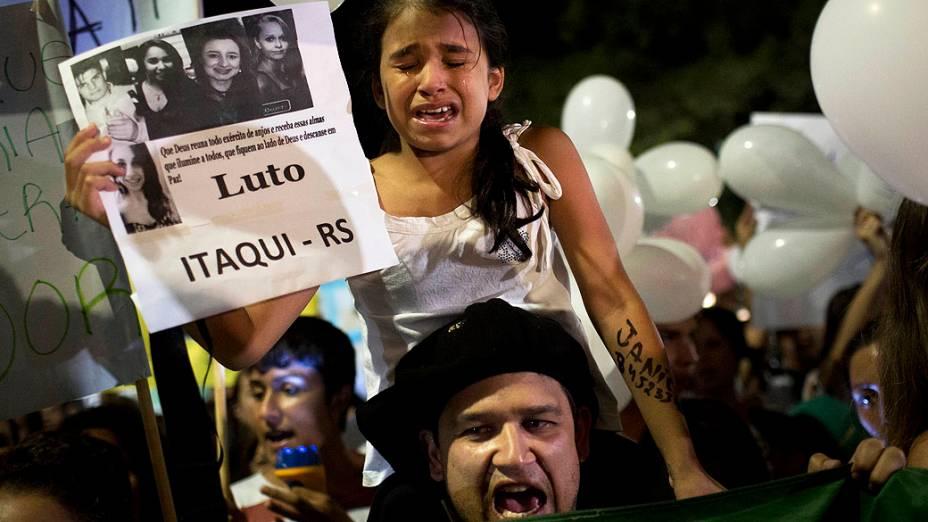 Menina chora sobre os ombros do pai segurando um cartaz mostrando fotos de vítimas do incêndio de Santa Maria (RS)