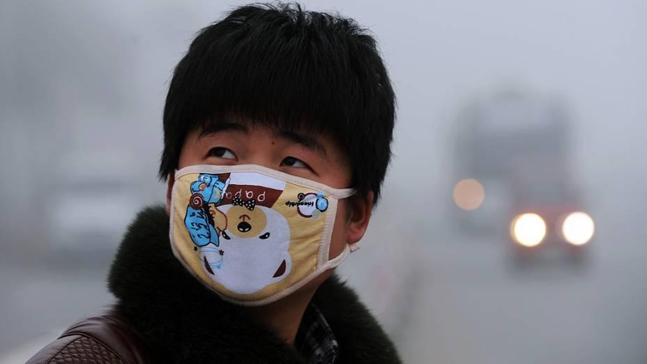 Jovem usa máscara para se proteger da poluição em Pequim, onde os níveis alarmantes de sujeira no ar fizeram com que as vendas de produtos desse tipo disparassem